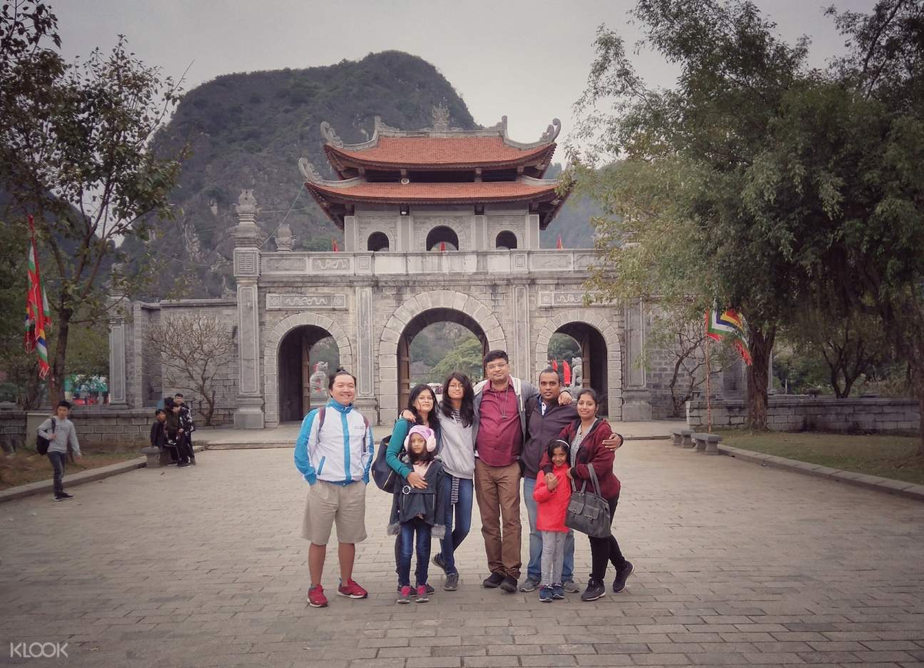 tourists posing in front of a temple in hoa lu